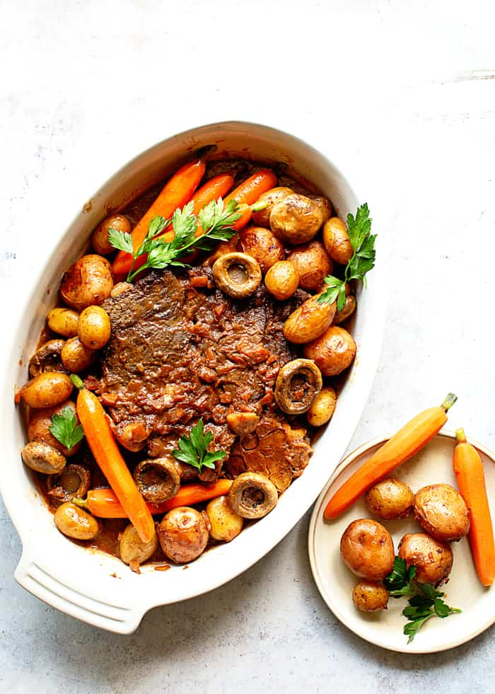 Overhead shot of delicious Pot Roast recipe with carrots, potatoes and parsley against white background