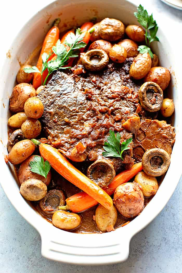 A large dish of pot roast with carrots, potatoes and mushrooms against back light