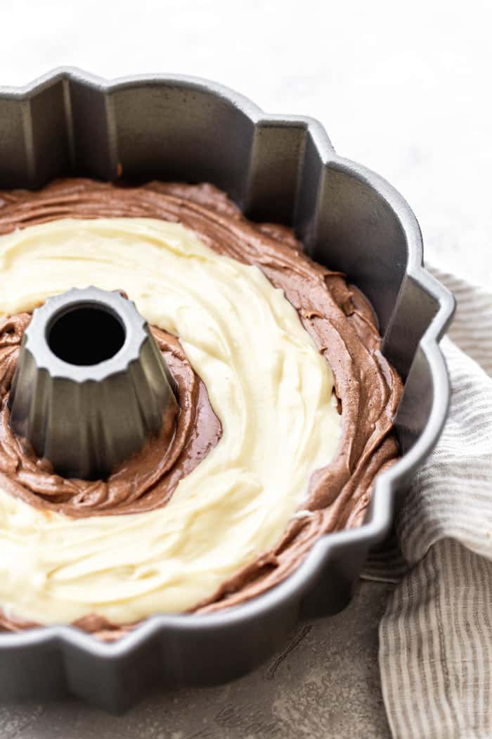 Cream Cheese Filling added to Baileys chocolate bundt cake batter ready to bake in bundt pan
