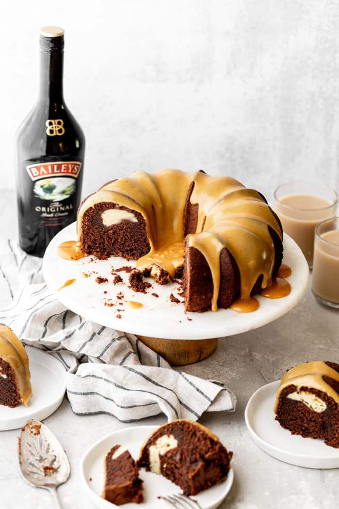 Sliced Baileys Chocolate Bundt Cake recipe with cream cheese filling on cake stand with slices around