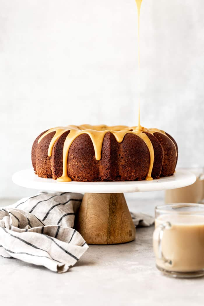 Chocolate bundt cake with caramelized white chocolate ganache glaze on white cake stand with glasses of Irish Cream ready to serve