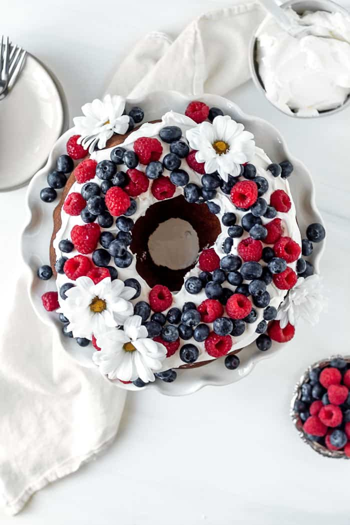Overhead shot of a butter pound cake recipe with whipped cream, raspberries and blueberries and edible flowers against white background ready to serve