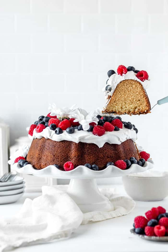 A slice of butter pound cake being lifted out of full cake with berries on white cake plate