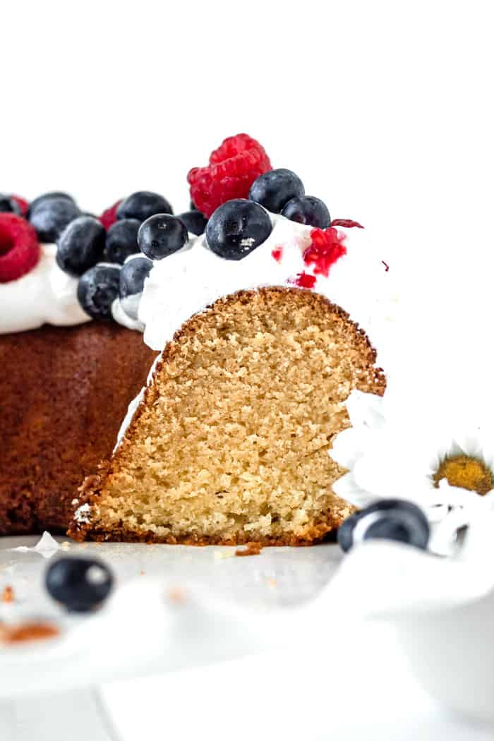 Close up of sliced old fashioned pound cake with whipped cream and berries ready to serve