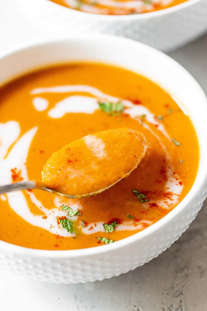 A spoon of creamy carrot ginger soup ready to serve