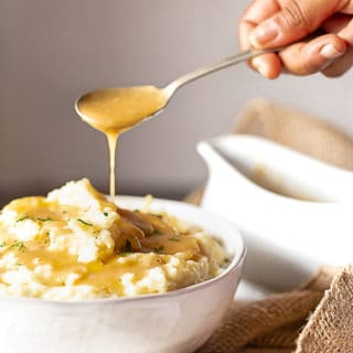 After learning how to make gravy from scratch, the homemade gravy is ladled over mashed potatoes