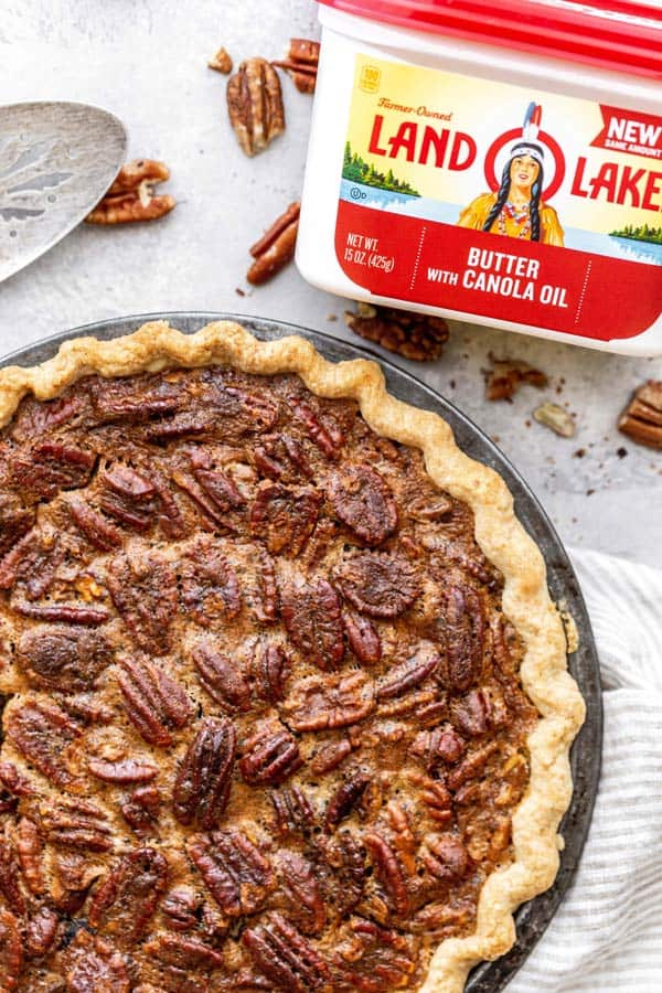 A large pecan pie against white background with pie server and butter package