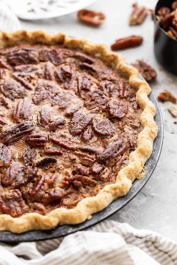 A close up pecan pie recipe with homemade crust with pecans surrounding it