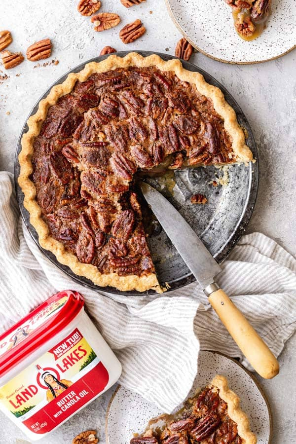 A half pecan pie recipe agains white background with butter