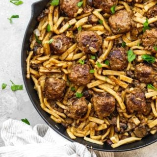A large skillet of salisbury steak meatballs and noodles in a large skillet over white background with parsley sprinkle