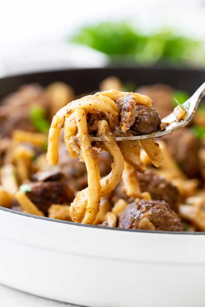 Egg noodles and mushrooms on fork from homemade Salisbury Steak meatballs skillet