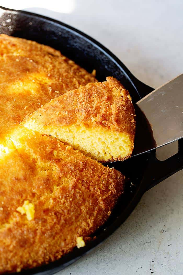 A slice of Southern cornbread being taken out of a cast iron skillet