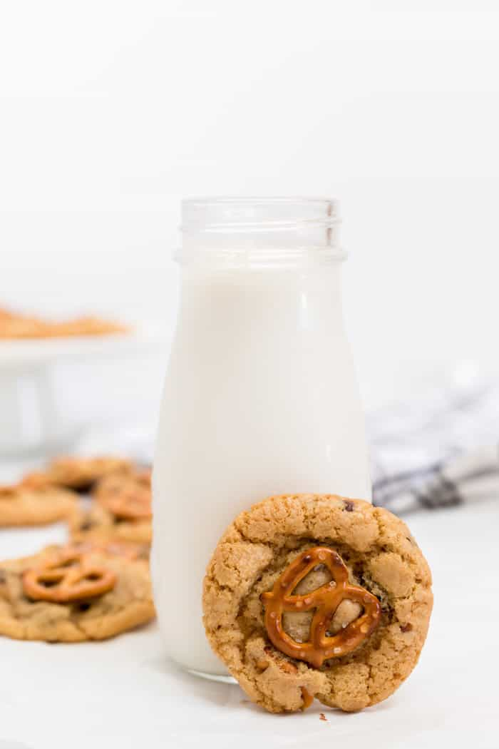 A homemade chocolate chip cookie next to glass of milk