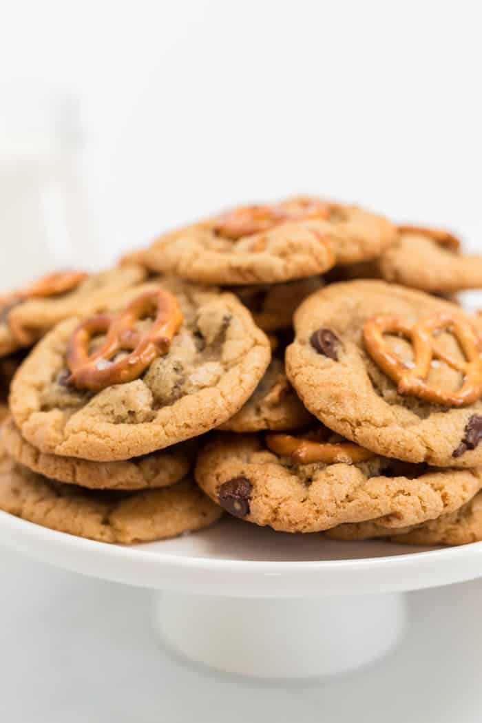 A white cake plate of homemade chocolate chip cookies with pretzels ready to serve