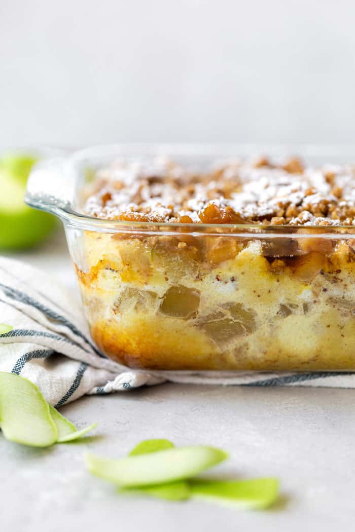 A powdered sugar sprinkled Apple Crisp French Toast Casserole ready to dig in with apples in background