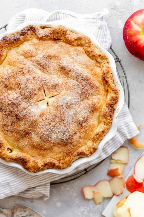 An overhead of a perfectly golden brown double crusted apple pie recipe against gray background with a red apple being peeled