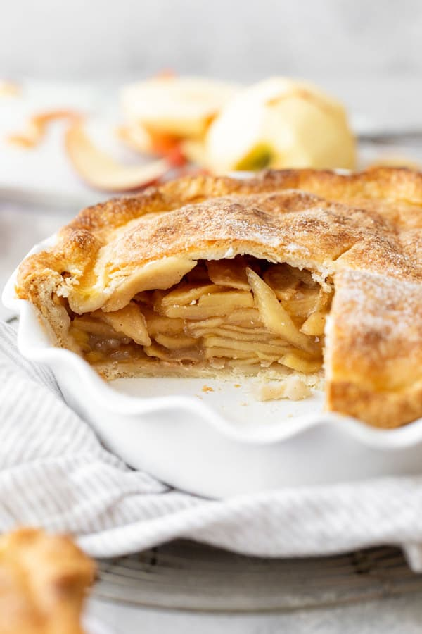 A close up of inside of the best apple pie recipe with peeled apple in the background