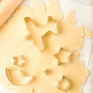 Sugar cookie dough rolled out with cookie cutters ready to cut out shapes