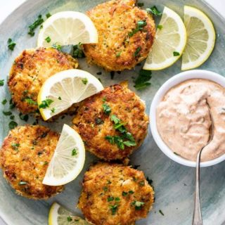 Gorgeous crab cakes scattered with lemon wedges and remoulade sauce ready to serve