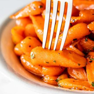 A close up of honey glazed carrots with fork pierced into one carrot