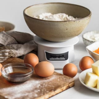 ingredients to bake with including flour, eggs, vanilla and butter set up