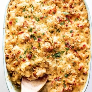 A delicious baked lobster mac and cheese recipe with spoon digging in to serve