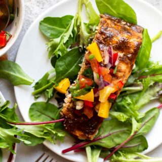 A close up of jerk seasoned salmon fillet with fruit salsa over spinach