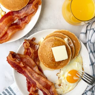 Pancakes piled high with butter, candied bacon and egg along with orange juice being served for breakfast