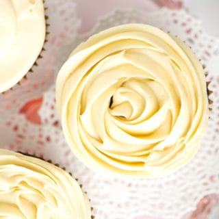 A close up of frosting piped on cupcake like a rose