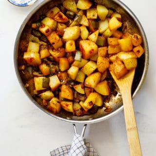 A large skillet of Smothered potatoes with a large spoon ready to serve