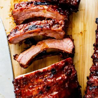 A close up of bbq ribs sliced and ready to serve with barbecue sauce