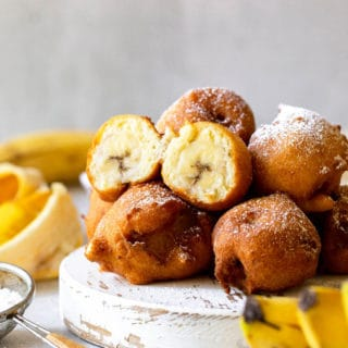 Fritters with banana filling piled high with powdered sugar