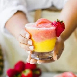 Two hands holding a half strawberry and half mango frozen wine slushy ready to serve