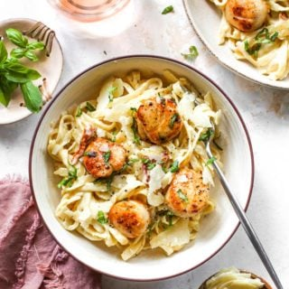 Two bowls of roasted garlic in a creamy pasta sauce with scallops against white background
