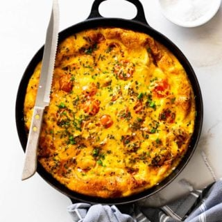 Perfectly baked frittata with tomatoes, potatoes and chicken fresh out of the oven against white background with gray towel