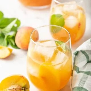 Peach sweet tea in two glasses surrounded by a pitcher, fresh peaches and mint