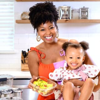 Mother and daughter smiling in kitchen holding frittata in food storage container