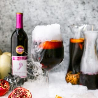 A delicious sangria recipe in a wine glass with dry ice next to a full carafe
