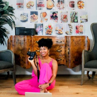 Jocelyn Delk Adams sitting on a floor holding a Canon camera n her laptop working with images of her brand on the wall behind her