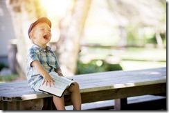 un petit garçon ri au éclat en lisant un livre