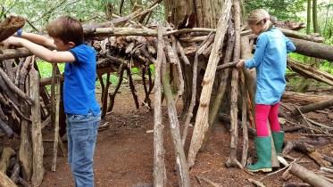 une fille et un garçon construisant une cabane en bois