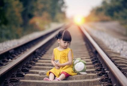 petite fille assise sur une ligne de chemin de fer avec son doudou