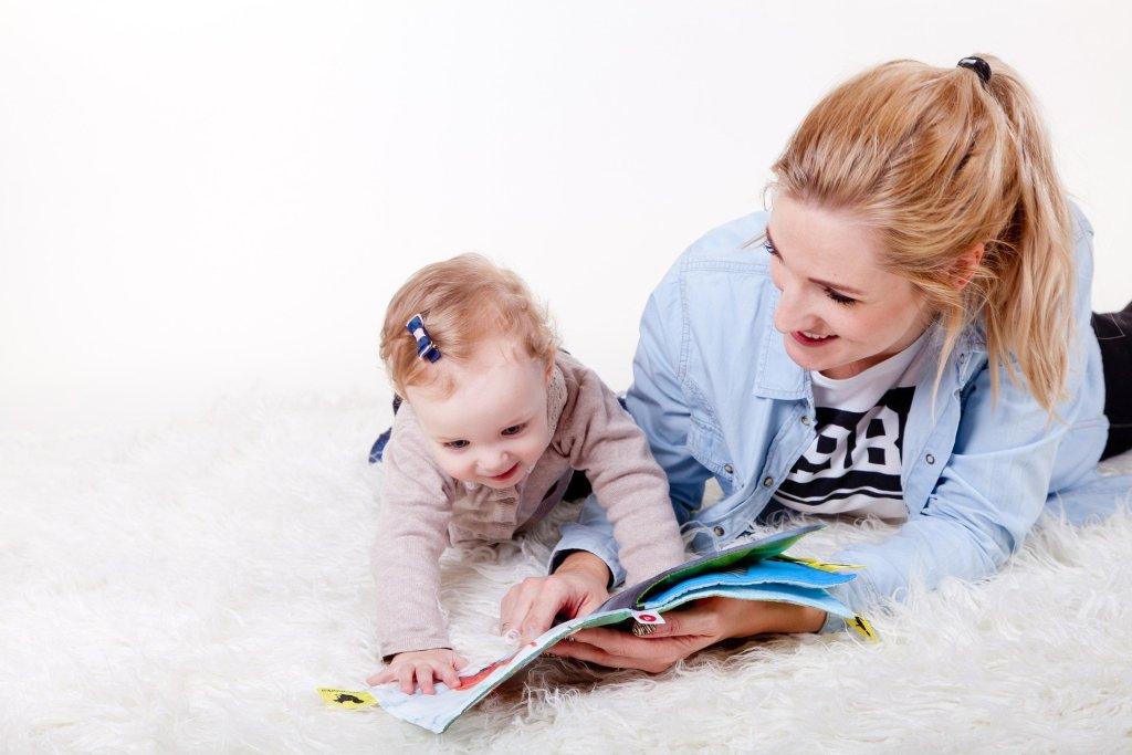 Une maman et sa fille en train de lire un album jeunesse.