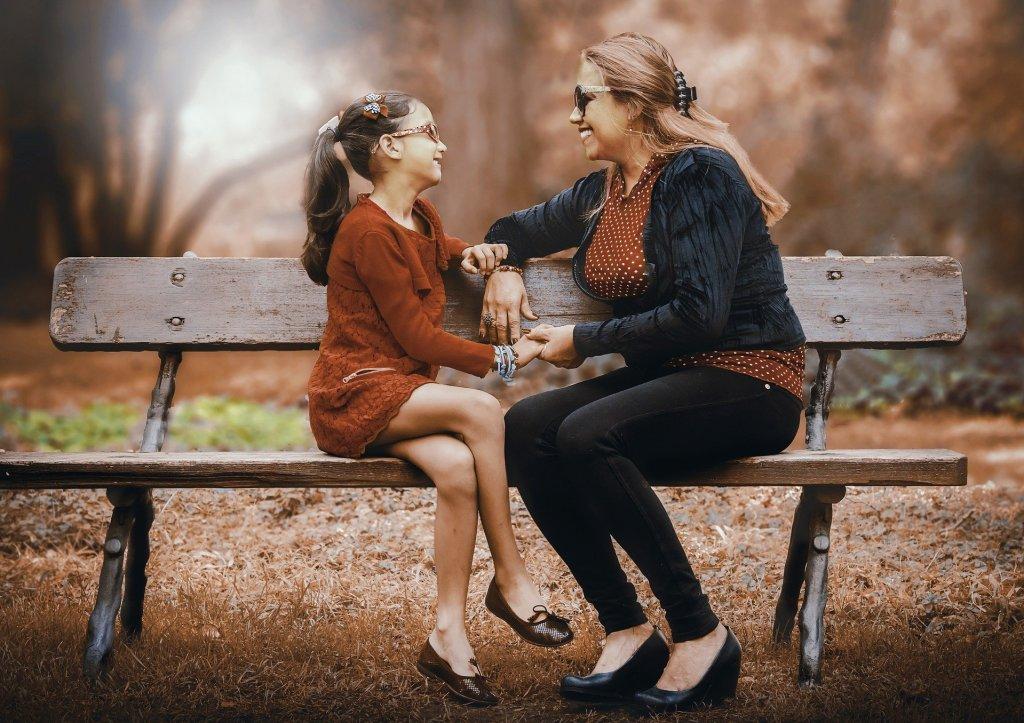 une mère et sa fille discutant sur un banc
