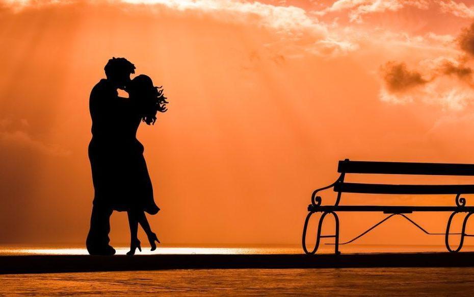 Couple qui s'embrasse sur un soleil orange