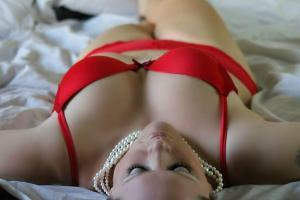 Femme en dessous rouge sur un lit