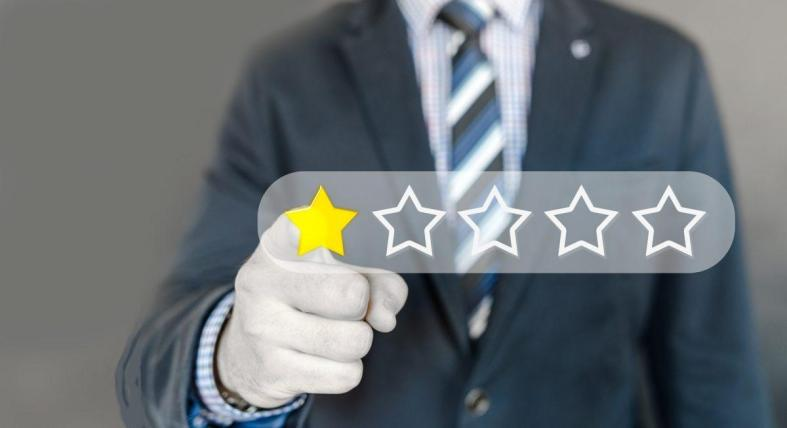Personne qui pointe sur une étoile pour une évaluation sur 5 étoiles