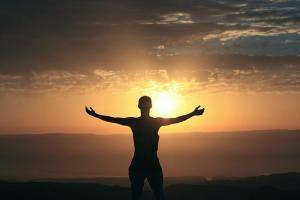 Homme les bras écarté vers le soleil