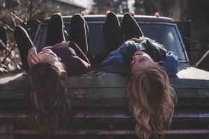 2 filles couchées sur la capot d'une voiture