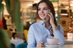 Femme passant un coup de file en buvant un café
